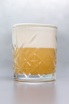 Cocktail met limoen en wit schuim in een glasglas.