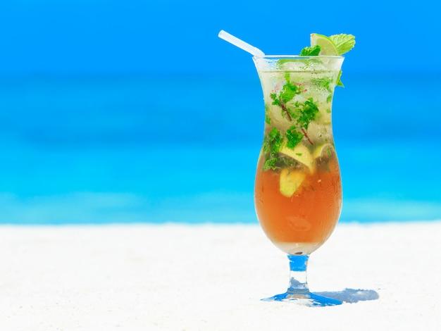 Cocktail met onduidelijk beeldstrand op achtergrond