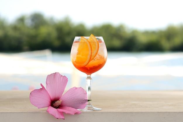 Cocktail met sinaasappel en ijs in een glastuimelschakelaar. met bloemdecor