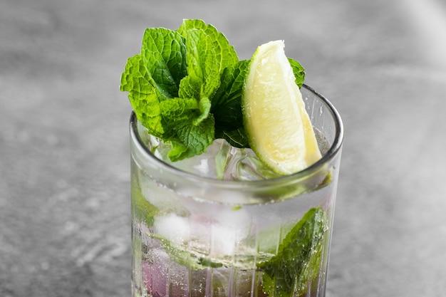 Cocktail met tonic, bessenstroop, limoen, munt, ijs in hoog glas op grijs oppervlak. bladerdeeg koud drankje met bosbessen.