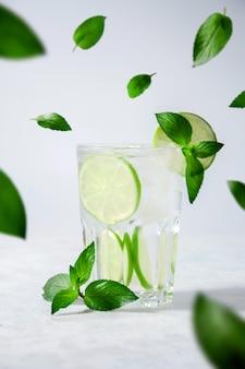 Cocktail mojito of limonade met limoen, munt en ijs. concept verse zomer drankjes.