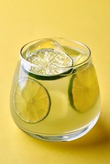 Cocktail van gin-tonic soda gegarneerd met een schijfje citroen op een gele achtergrond.