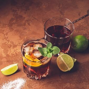 Cocktail van rum en cola ijsblokjes en limoen in glazen bekers op donkerbruin