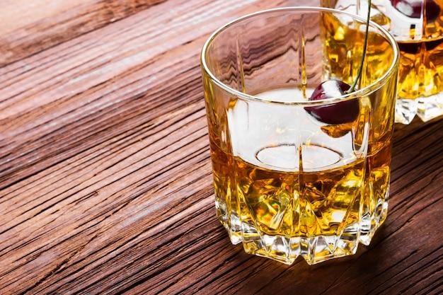 Cocktail van whisky met kers in twee glazen