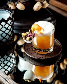 Cocktail versierd met sinaasappelschil en gedroogde bloemen