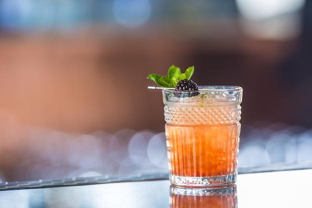 Cocktaildrank braamstruik met zwarte bessen en munt aan de bar in nachtclub of restaurant.