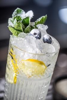 Cocktaildrank met bosbessen en munt bij barcounter in nachtclub of restaurant.