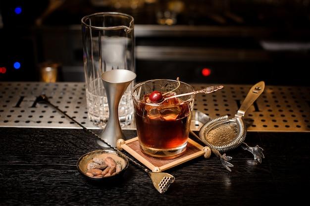 Cocktailglas gevuld met sterke en zoete zomercocktail versierd met kersen