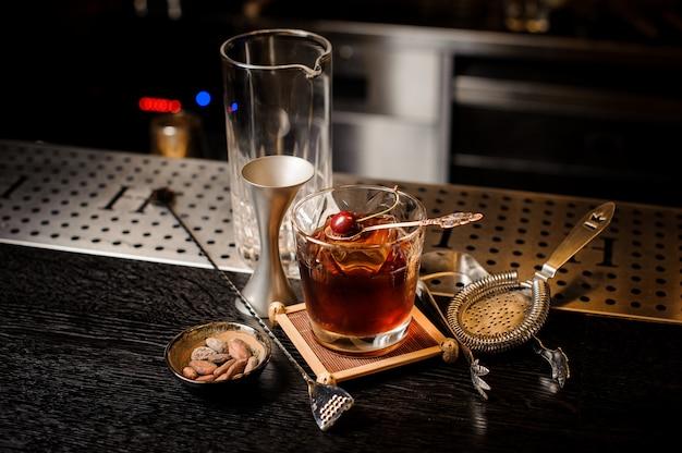 Cocktailglas gevuld met sterke en zoete zomercocktail versierd met verse kers op kleine lepel