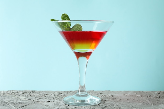 Cocktailglas met aardbei en oranje gelei op blauwe achtergrond