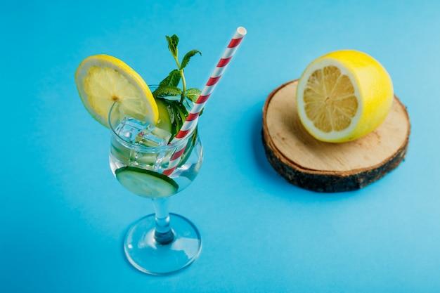 Cocktailkomkommerwater met citroen en munt in een glas op een servet op een blauwe achtergrond in de buurt van citroen en komkommer. horizontale foto