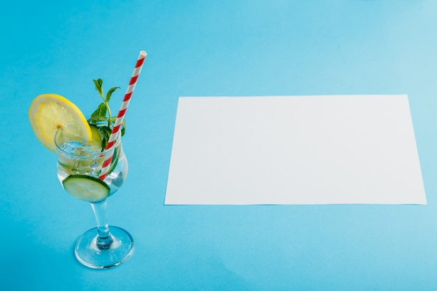 Cocktailkomkommerwater met citroen en munt in een glas op een servet op een blauwe achtergrond.