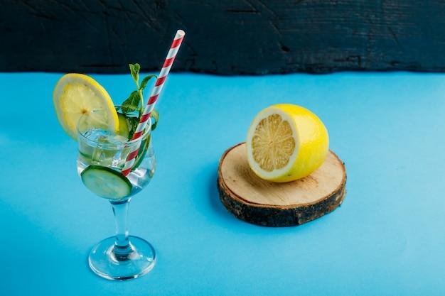 Cocktailkomkommerwater met citroen en munt in een glas op een servet op een blauwe ondergrond in de buurt van citroen en komkommer