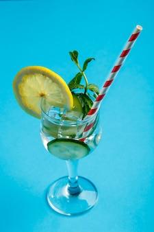 Cocktailkomkommerwater met citroen en munt in een glas op een servet op een blauwe ondergrond