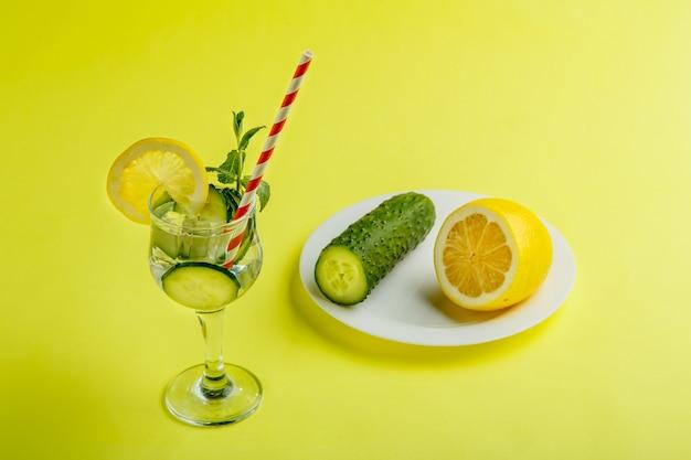 Cocktailkomkommerwater met citroen en munt in een glas op een servet op een gele achtergrond naast komkommers en citroen op een servet.