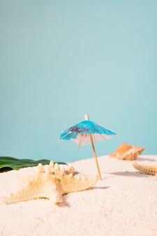 Cocktailparaplu en zeester op strand