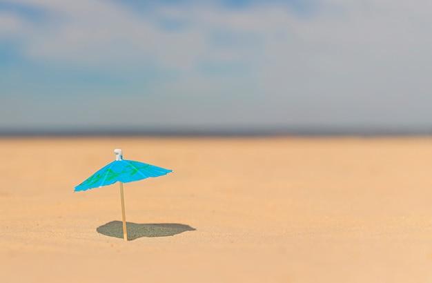 Cocktailparaplu op een leeg strand tegen een vage zee.