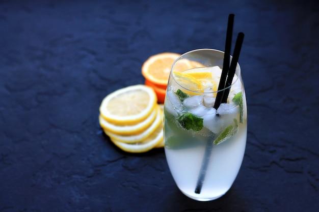 Cocktails met ijs in hoge glazen met fruit en cocktailbuizen op een donkere achtergrond
