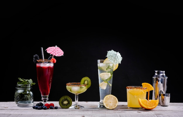 Cocktails van verschillende vruchten in kristallen glazen op een houten bord