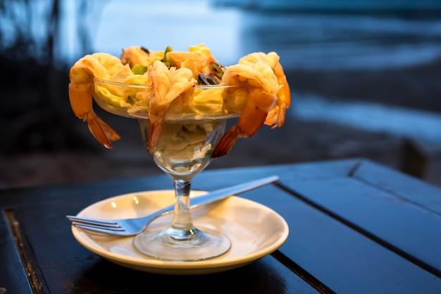 Cocktailsalade met garnalen en zeevruchten op een houten tafel tegen de achtergrond van de zee