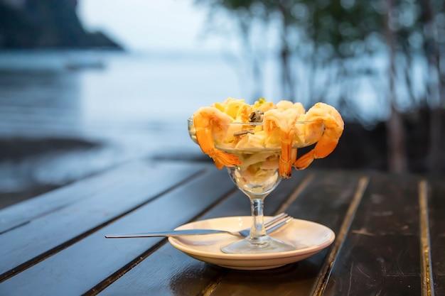 Cocktailsalade met garnalen en zeevruchten op een houten tafel tegen de achtergrond van de zee.