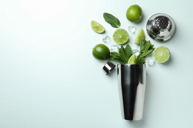 Cocktailshaker en ingrediënten voor mojito op witte achtergrond