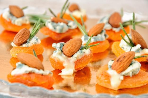 Cocktailsnack van gedroogde abrikozen met gorgonzola en amandelen