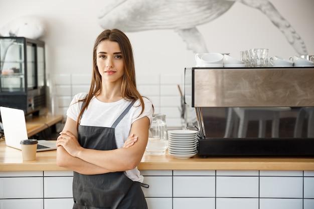Coffee business owner concept - portret van gelukkige aantrekkelijke jonge mooie kaukasische barista in de schort met zelfverzekerd kijken naar de camera in de koffiewinkel counter.