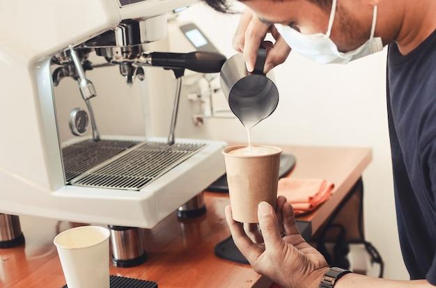 Coffee latte barista maakt patroon in een kopje koffieshop