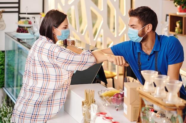 Coffeeshop-barista en vrouwelijke klant met medische maskers die elleboogstoten maken wanneer ze elkaar begroeten