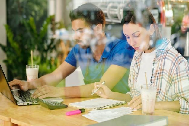 Coffeeshop-barista werkt op laptop wanneer zijn collega de financiën beheert en bonnen controleert
