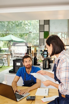 Coffeeshop eigenaren zitten aan tafel en bespreken financiën, inkomen en