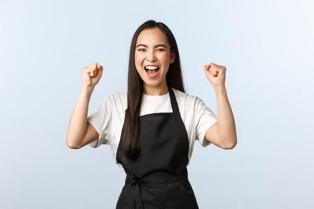 Coffeeshop, klein bedrijf en startup concept. aangemoedigde gelukkige aziatische vrouwelijke barista, meisjeswerknemer in café in zwarte schort, handen omhoog en ja schreeuwen, succes vieren of winnen.
