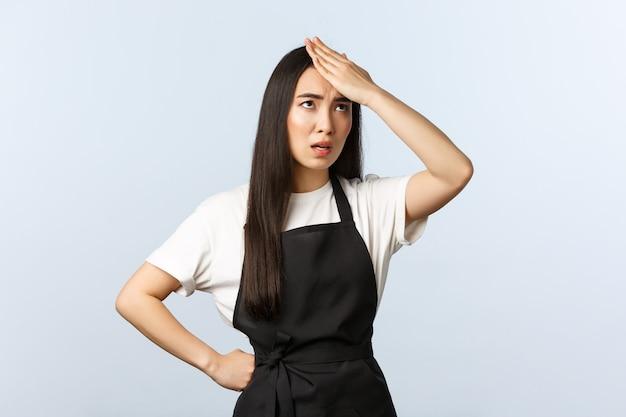 Coffeeshop, klein bedrijf en startup concept. geërgerde en beu vrouwelijke barista moe van vreemde klanten, facepalm, voorhoofd slaan en oogrollen van ergernis, zwarte schort dragen