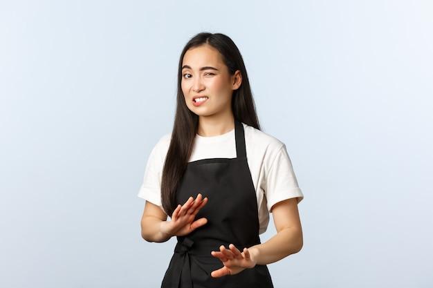 Coffeeshop, klein bedrijf en startup concept. onhandige en ontevreden jonge vrouwelijke barista die een vreemde klant probeert te kalmeren, een ontspannen of chill gebaar laat zien en ineenkrimpt voor iets walgelijks