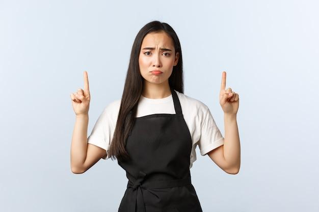 Coffeeshop, klein bedrijf en startup concept. sombere trieste schattige restaurantkelner die met de vingers omhoog wijst. boos vrouwelijke aziatische barista in zwarte schort met slecht nieuws op de bovenste banner, mokken?