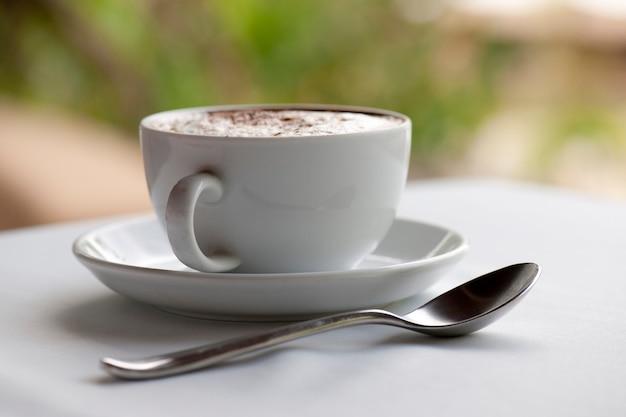 Cofffee kop, schotel en theelepel, gevuld met gestoomde melk en besprenkeld met kruiden, op een witte tafel