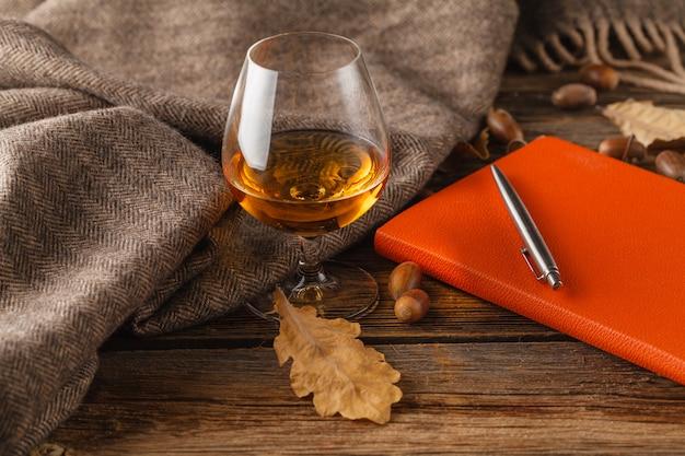 Cognac en rood boek met de herfstbladeren op houten lijst - seizoengebonden ontspan concept
