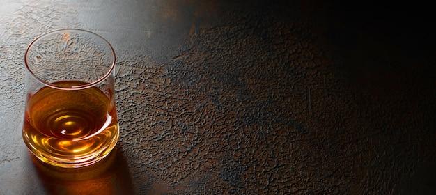 Cognac of bourbon of rum in glazen glazen op een donkerbruine achtergrond. kopieer ruimte