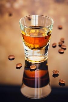 Cognac of likeur, koffiebonen en kruiden op een glazen tafel
