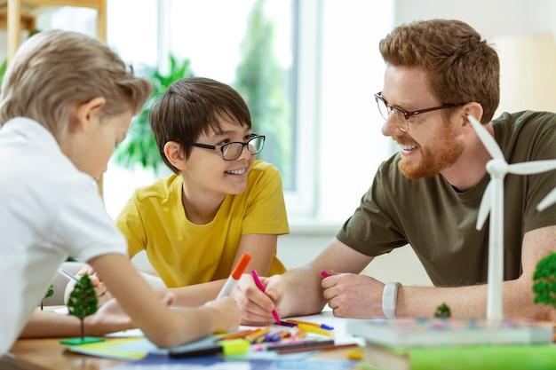Cognitief project. lachende kortharige man met een heldere bril die kleine jongens helpt met een projectieve poster voor zijn lessen