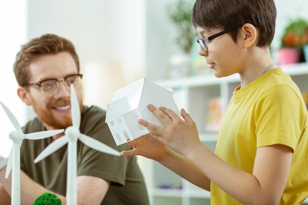 Cognitieve lessen. nieuwsgierige donkerharige jongen die een wit plastic huis vasthoudt terwijl hij een voorbeeld van een windmoleninfrastructuur observeert