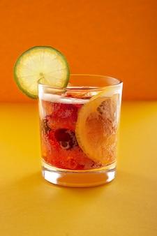 Cola met ijs, schijfje citroen en limoen op oranje muur