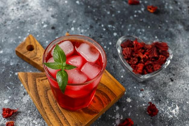 Cold brew hibiscusthee met ijs en basilicumblaadjes.