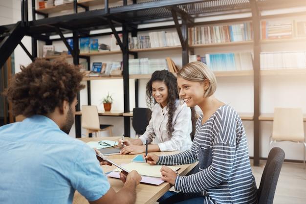 Collaboratief werk. groep jonge projectmanagers die aan nieuwe start, analyseplannen werken. drie perspectief professionele jongeren die in moderne bibliotheek op vergadering zitten.