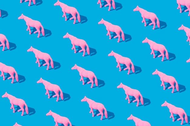 Collage van roze rubberen paarden geïsoleerd op blauwe achtergrond. isometrische rechthoek lay-out. minimaal abstract concept