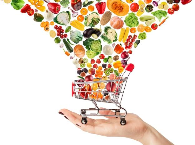 Collage van winkelwagentje met groenten en fruit geïsoleerd