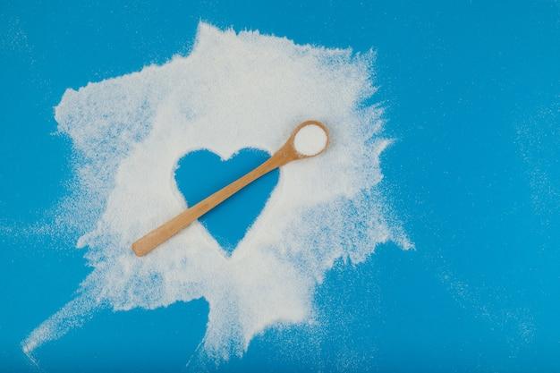 Collageenpoeder of -eiwit is chaotisch verspreid over een blauw oppervlak. lege ruimte in de vorm van een hart. de bamboelepel imiteert een pijl. gezond voedingssupplement.