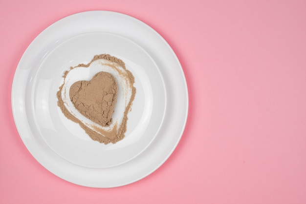 Collageenpoeder of eiwit wordt willekeurig over het oppervlak van de plaat verspreid. hartvormige lege ruimte. aanvulling op een gezond voedingspatroon. 14 februari.