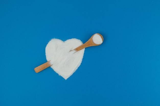 Collageenpoeder of proteïne op blauwe achtergrond. gezond voedingssupplement. poeder dat in de vorm van een hart wordt gegoten met een lepel die een pijl imiteert.